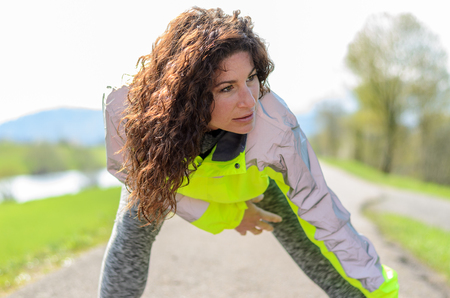 high visibility: Smiling attractive woman wearing a luminous high visibility jacket working out on a rural road, close up
