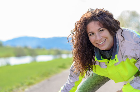 high visibility: Smiling attractive woman wearing a luminous high visibility jacket working out on a rural road, close up of her face