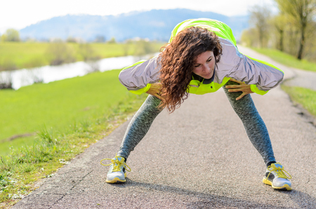 limbering: Attractive fit young woman doing a physical workout as she stretches her muscles to warm up before going jogging on a rural lane