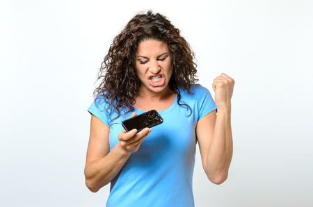 anguish: Emotional woman holding a broken mobile phone reacting in anguish or frustration with closed eyes and open mouth