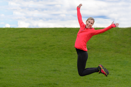 フィットの健康な女性の喜びのためにジャンプがコピー スペースとした農村緑地上両腕とフレンドリーな笑顔で空中を表示 写真素材