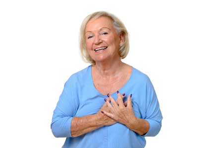 heartfelt: Elderly woman holding her hands to her heart in gratitude and appreciation with a beaming smile of pleasure, upper body isolated on white