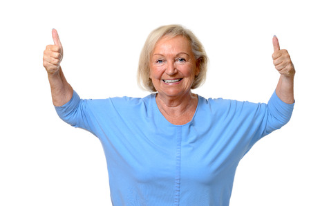 motivated: Enthusiastic motivated senior woman with a beaming smile giving a double thumbs up gesture to show her approval and success,upper body isolated on white Stock Photo
