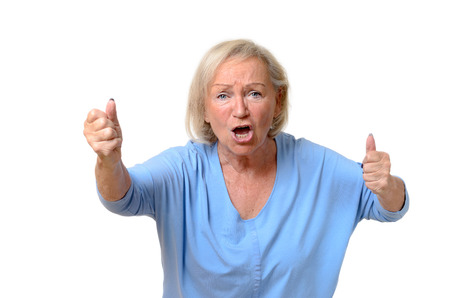 irate: Emotional single senior woman dressed in blue blouse with angry expression and clenched fists over white background