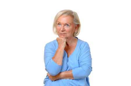 upper body: Thoughtful attractive blond elderly woman staring up into the air with her chin resting on her hand, upper body isolated on white Stock Photo