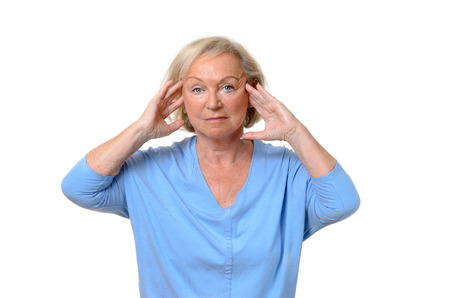 throbbing: Attractive elderly lady suffering from a headache holding her hands to her temples as she stares glumly at the camera in a health and wellness concept, upper body isolated on white Stock Photo