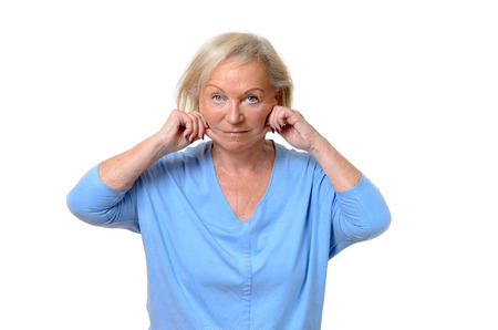 ageing: Elderly woman pulling at the skin on her jowls or cheeks pinching it between her fingers showing the ageing process in a beauty concept, upper body isolated on white