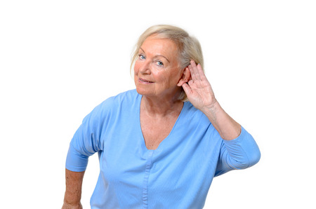 deafness: Hard of hearing attractive elderly woman holding her hand behind her ear to aid her deafness as she listens attentively, upper body isolated on white
