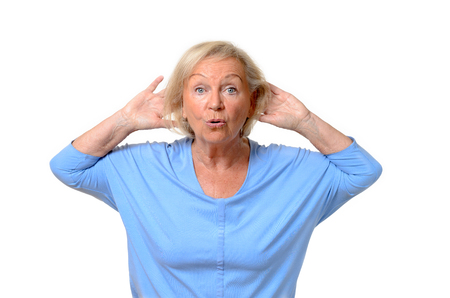 hands behind head: Wide-eyed single senior woman in blue shirt with hands behind head and surprised or amazed expression