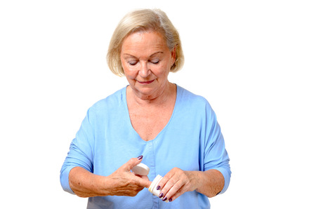 upper body: Elderly woman taking cosmetic cream, moisturizer or mask from a jar with her finger to put on her face in a skincare concept, upper body isolated on white