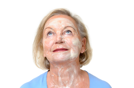 ageing: Smiling elderly lady with face cream on her skin standing looking up into the air with lovely blue eyes in a beauty, ageing and skincare concept, close up head shot over white with copy space