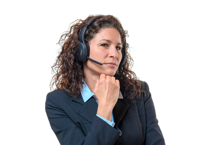 speculative: Speculative attractive young businesswoman wearing a headset looking sideways at the camera with a serious distrustful expression, isolated, on white
