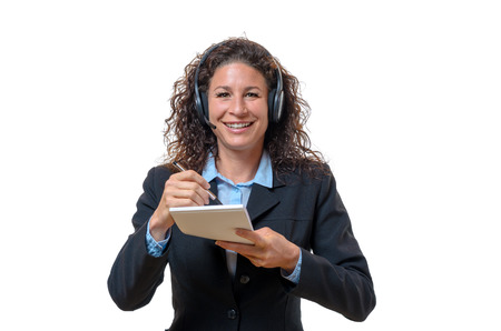 personal call: Smiling friendly businesswoman in a headset holding a notepad and pencil in front of her chest conceptual of a secretary, call center operator or personal assistant