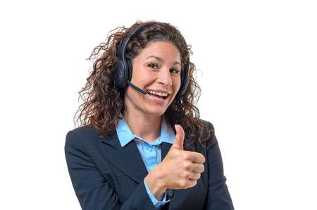 Entusiasta joven y atractiva de negocios que llevaba un auricular dando un pulgar hacia arriba gesto de éxito y la aprobación con una amplia sonrisa, parte superior del cuerpo en blanco Foto de archivo