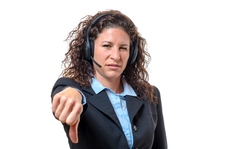 disapproval: Young businesswoman wearing a headset signalling her disgust and disapproval with a thumbs down gesture, isolated on white