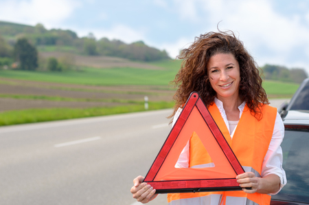 breaking down: Pretty young woman holding a red triangular traffic warning sign in her hands as she prepares to place it on the road behind her vehicle after breaking down at the roadside Stock Photo