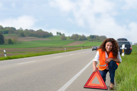 breaking down: Smiling attractive woman putting out a traffic warning sign on the shoulder of the highway after breaking down in her car