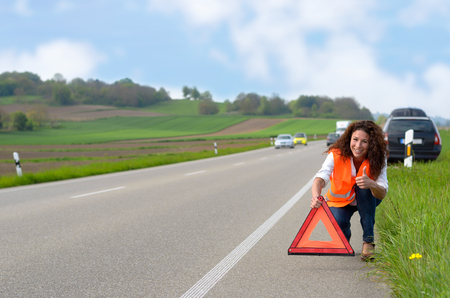 breaking down: Smiling attractive woman putting out a traffic warning sign on the shoulder of the highway after breaking down in her car and giving thumb up gesture Stock Photo
