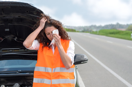 high visibility: Upset young woman crying after a car breakdown standing wiping tears from her eyes in front of the vehicle at the roadside with the bonnet raised Stock Photo
