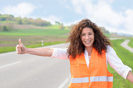 breaking down: Smiling confident young woman wearing a high visibility jacket standing at the roadside hitching a lift after breaking down in her car