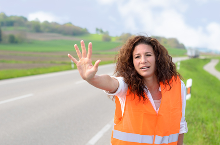 frantic: Frantic young woman in a high visibility jacket standing at the side of a rural road trying to stop traffic by raising her palm after breaking down in her car Stock Photo