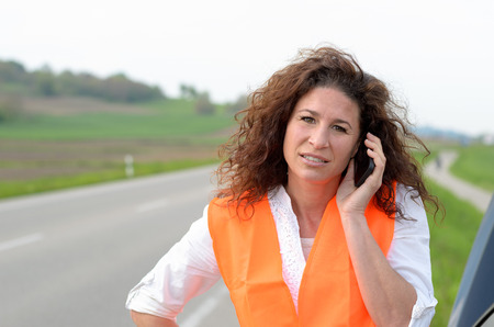 summoning: Despondent attractive young female driver trying to summon help on her mobile phone after breaking down at the roadside on a rural highway in her car