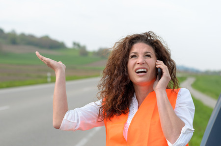 irked: Exasperated young female driver talking to roadside assistance on her mobile phone after breaking down in her car on a rural road gesturing angrily with her hand Stock Photo