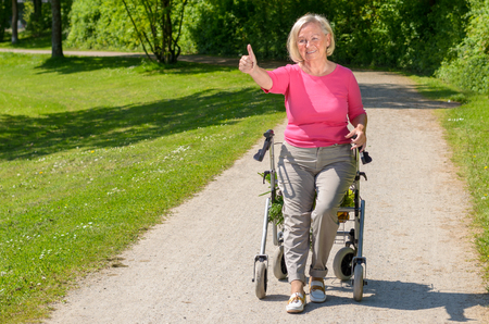 Elderly woman wearing pink blouse sits in wheeled walker on park path while smiling and holding a thumbs up