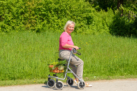 Smiling elderly woman wearing pink blouse while seated in walker with wheels on park path