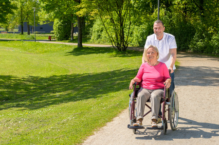 park path: Elderly woman seated in wheel chair by standing husband on a park path on a bright summer afternoon