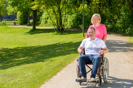 pushes: Man seated in wheel chair while wife wearing pink blouse pushes him down park path on a sunny afternoon