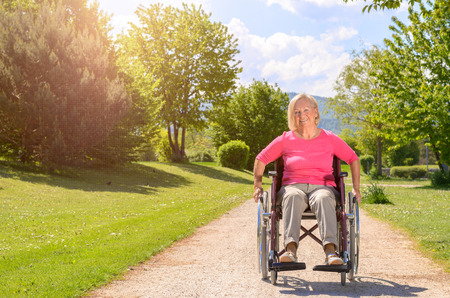 park path: Elderly woman smiles while seated in wheel chair on a beautiful summer day rolling down a rocky park path