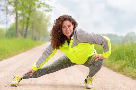 limbering: Sporty attractive young woman in a high visibility jacket doing stretching exercises to warm up before going jogging an a rural dirt road, smiling at camera Stock Photo