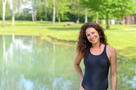 bathing costume: Smiling fit young woman in a bathing costume standing at the side of a rural lake looking at the camera, with copy space
