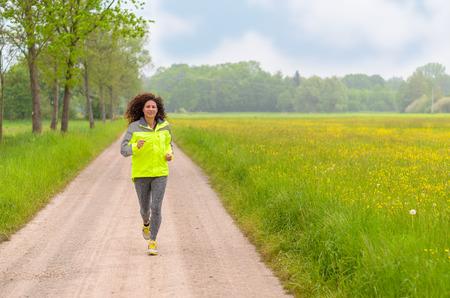 cardiovascular workout: Fit young woman enjoying her morning run through lush green spring meadows as she jogs down a dirt road towards the camera Stock Photo
