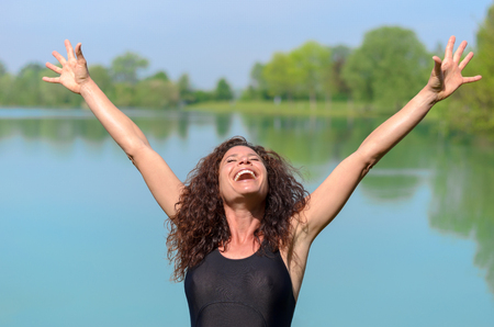 exhilaration: Pretty young woman in a bathing suite rejoicing in spring sunshine laughing and extending her arms into the air against a rural lake backdrop