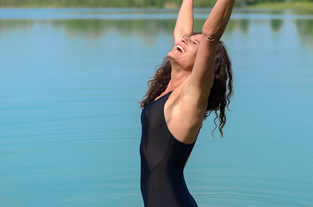 reaching up: Beautiful single woman with big smile in bathing suit reaching up in front of shallow lake in background