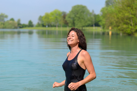 Beautiful single woman with joyous smile in bathing suit wading in shallow lake with green trees in background
