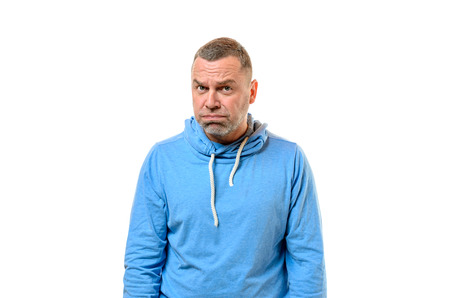 Single grumpy man with gray haired beard in blue drawstring hooded sweater near white wall Stock Photo