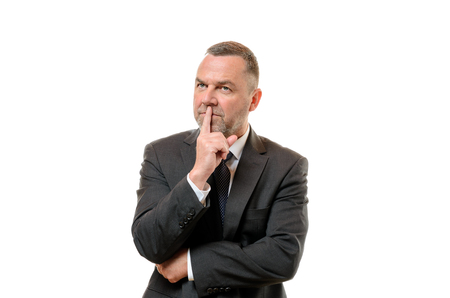 contemplative: Thoughtful businessman standing with his finger to his lips staring up into the air with a contemplative expression, on white Stock Photo