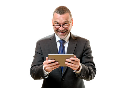 beaming: Happy satisfied businessman holding a tablet in his hands and peering over his glasses at the camera with a beaming smile of success, isolated on white