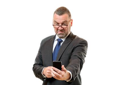 contempt: El hombre de negocios tirando de la cara desdeñosa de disgusto mientras lee un mensaje en su teléfono móvil celebrado en longitud de los brazos, parte superior del cuerpo en blanco