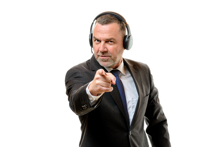 identifies: Irate middle-aged businessman wearing headphones pointing a finger of blame as he identifies something or makes an accusation, on white Stock Photo