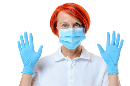 nurse gloves: Close up of red headed nurse wearing face mask and blue rubber gloves while staring at camera and against a white background Stock Photo