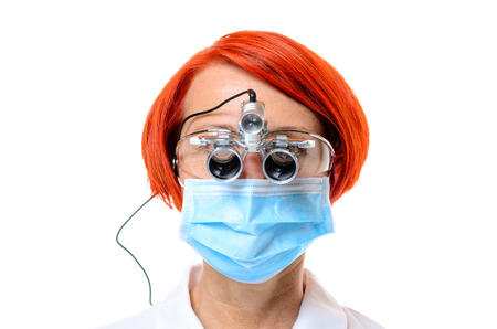 white headed: Red headed female doctor wearing surgical scope and a blue face mask against a white background Stock Photo
