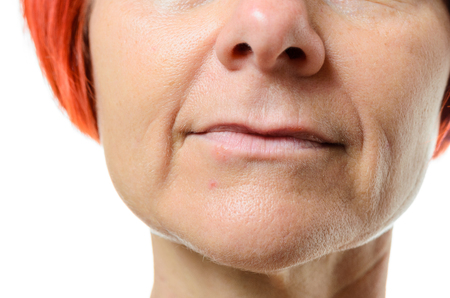 labialis: Extreme close up of older woman with red hair with a blemish on her face against a white background Stock Photo