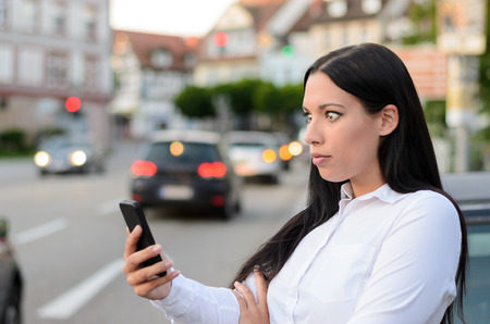 wide eyed: Incredulous attractive young woman standing in a busy street in town reading a text message on a mobile phone with wide eyed disbelief