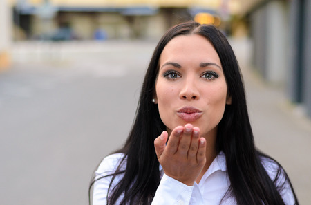 kissing mouth: Gorgeous seductive woman blowing a kiss at the camera over the palm of her hand as she stands in a deserted urban street with copy space Stock Photo