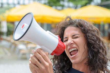 airs: Attractive angry woman shouting into a megaphone outdoors n an urban square as she airs her grievances during a protest Stock Photo