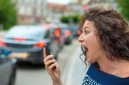 horrified: Aghast attractive young woman with a horrified expression looking at a text message on her mobile phone as she stands on a busy urban street, close up head and shoulders